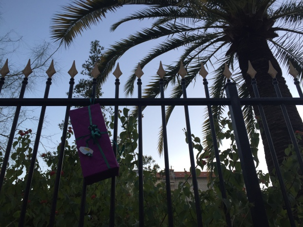 Gifts for the homeless left with greetings by children fixed to park fencing in Nice, December 2016